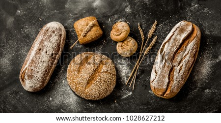 Bakery - gold rustic crusty loaves of bread and buns on black chalkboard background. Still life captured from above (top view, flat lay), banner layout. #1028627212