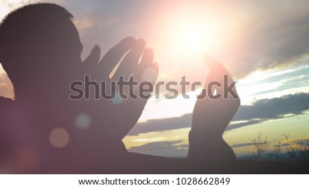 Silhouette of young muslim man praying outside during sunset with lens flare #1028662849