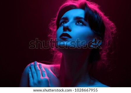 serious young woman in multicolor lights on black background looking up #1028667955
