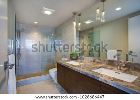Modern high-rise master bathroom features dual vanity cabinet with undermount sinks, grey marble counter top and large walk in shower.