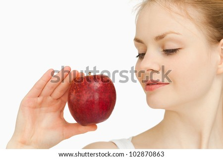 Woman holding an apple while looking at it against white background #102870863