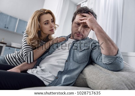 Calm down. Tired depressed unemployed man sitting on a sofa and thoughtfully touching his forehead while his caring loving wife looking attentively at him #1028717635