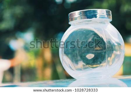 Transparent empty small glass jar outdoor #1028728333