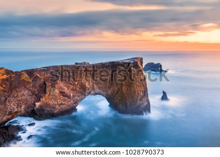 Dyrholaey rock formation at sunset. Dyrholaey is a promontory located on the south coast of Iceland, not far from the village Vik #1028790373