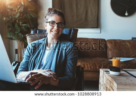Pretty woman with laptop sitting in cozy loft apartment #1028808913