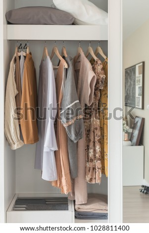 wooden wardrobe with clothes hanging on rail, interior design concept #1028811400
