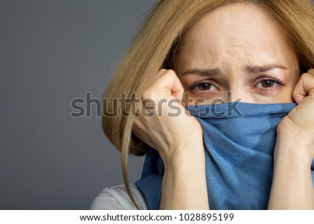 Protection concept. Depressed blonde lady covering her mouth with clothes and wrinkling her forehead expressing pain. Copy space in left side. Isolated on background #1028895199
