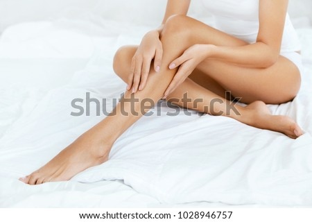 Long Woman Legs With Smooth Soft Skin. Close Up Of Female With Perfect Healthy Silky Legs Skin After Hair Removal On White Bed In Light Interior. Beauty, Skin Care Concept. High Resolution. #1028946757