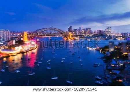 Dark illuminated architecture landmarks of Sydney city around Harbour as seen from North Sydney towards Sydney Harbour bridge. #1028991541