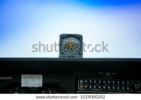 Macro shot of compass. Aircraft equipment, various indicators, buttons, instruments. The flight desk and control panel during take off and landing. Aircraft dashboard panel in pilot school #1029000202