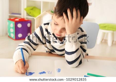 Cute little boy doing homework indoors #1029012835