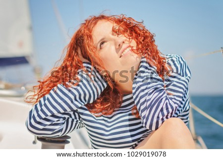 Beautiful red-haired girl enjoys the sun on a yacht / copy space #1029019078