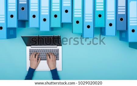 Organized archive with ring binders and woman searching for files in the database using a laptop, top view #1029020020