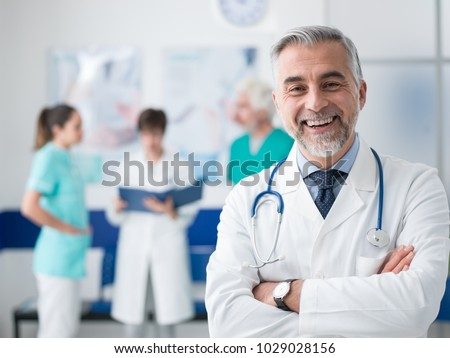 Confident smiling doctor posing and the hospital with arms crossed and medical team working on the background #1029028156