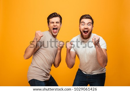 Portrait of a two cheerful young men celebrating isolated over yellow background #1029061426