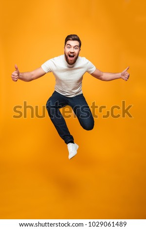 Full length portrait of an excited bearded man jumping and showing thumbs up isolated over yellow background Royalty-Free Stock Photo #1029061489