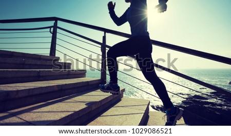 sporty female runner running upstairs on coast trail #1029086521