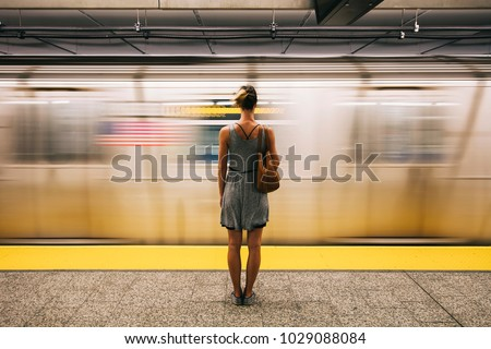 Rear view at young woman waiting for subway train in New York City, USA #1029088084