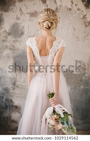 bride's back in lace dress with a bouquet Royalty-Free Stock Photo #1029114562