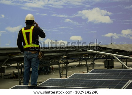 Foreman supervises the installation of solar cells. #1029142240