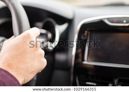 Closeup shot of a man's hand holding steering wheel while driving a car #1029166315