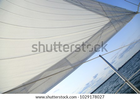Image of a sail full of wind against a blue sky on a large sailboat. #1029178027