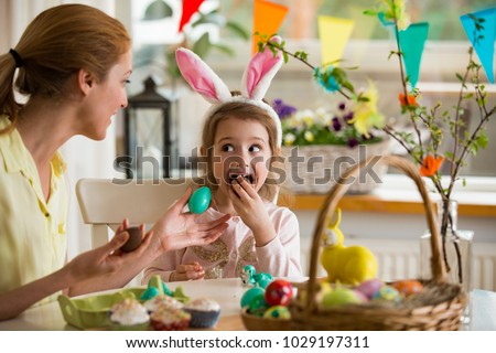 Mother and daughter celebrating Easter, eating chocolate eggs. Happy family holiday. Cute little girl with funny face in bunny ears laughing, smiling and having fun. Royalty-Free Stock Photo #1029197311