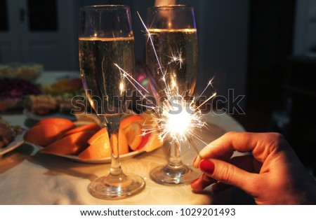 Bengal lights in hand against the background of a glass of champagne and food #1029201493