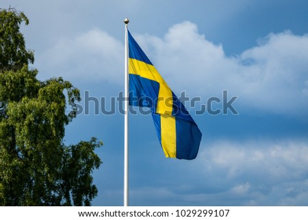 The Swedish blue and yellow banner on a pole waving in sunshine and blue cloudy sky #1029299107
