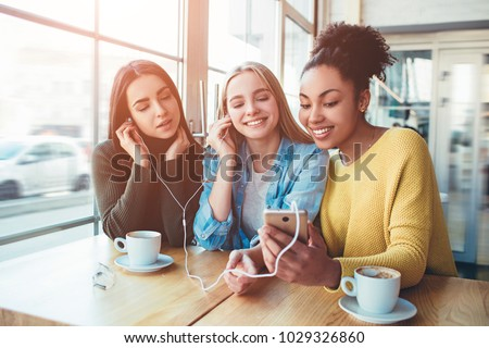 Three young women that are smiling. They closed her eyes and enjoying the music on smartphone. Best friends are sitting in cafe #1029326860