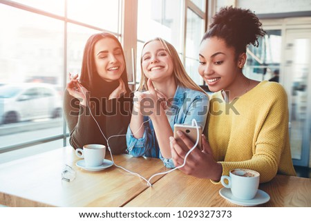 girls that are smiling. One of them has closed her eyes and enjoying the moment. The second one is dreaming about something good and adorable while the third one is trying to take a selfie. #1029327373