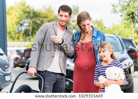 Mother, father, and child buying car at dealership, a new family auto #1029355669