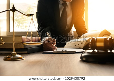 Male lawyer working with contract papers and wooden gavel on tabel in courtroom. justice and law ,attorney, court judge, concept. #1029430792