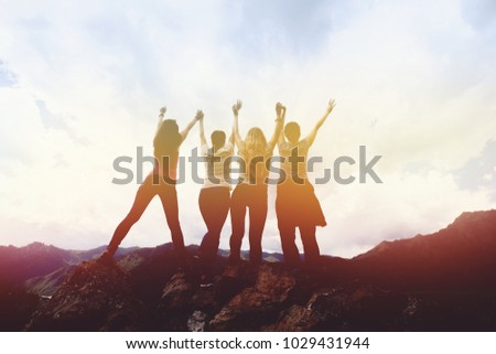 Happy friends having fun and top hand in mountains range and sky backdrop. Sunset #1029431944