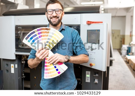 Funny portrait of typographer standing with color swatches at the printing manufacturing #1029433129