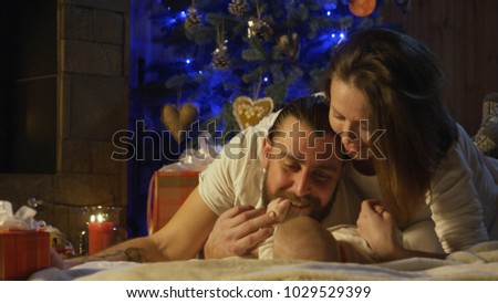 Young loving parents playing with their newborn baby in front of a decorated Christmas tree with lights at night spending time together. #1029529399