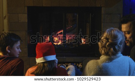 Loving parents with kids sitting at fireplace before New Year enjoying holiday together. #1029529423