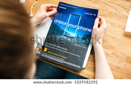PARIS, FRANCE - APR 26, 2017: Woman reading Unbox Your Phone advertising campaign for Samsung Galaxy Smartphone S8 in French from Orange Telecom in magazine newspaper #1029582292
