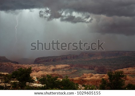 Lightning / dust  storm on Gold Bar Rim in  Moab Canyon in Moab Utah.  Empty space for text, quote, or saying on sky background. #1029605155