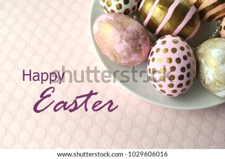 Decorated Easter eggs  in blush pink, peach and gold on a light pink pastel background with an ultra violet Happy Easter lettering sign for greeting cards and design. Flat layout with top view. #1029606016