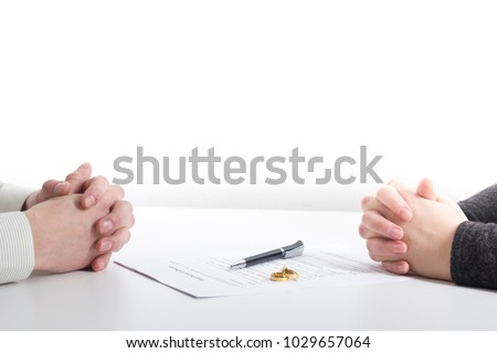 Hands of wife, husband signing decree of divorce, dissolution, canceling marriage, legal separation documents, filing divorce papers or premarital agreement prepared by lawyer. Wedding ring #1029657064