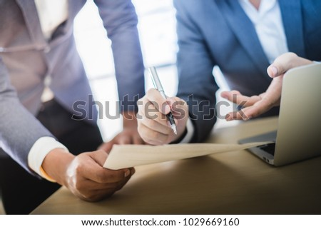 Business partners discussing documents and ideas at meeting Royalty-Free Stock Photo #1029669160