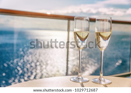 Luxury cruise ship travel champagne glasses on balcony deck with ocean sunset view on Caribbean vacation. Drinks in sun flare on cruise holiday destination. #1029712687