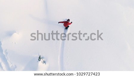 Snowboarding Overhead Top Down View of Snowboarder Riding Through Fresh Powder Snow Down Ski Resort or Backcountry Slope - WInter Extreme Sports Background #1029727423