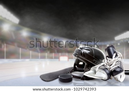 Ice hockey helmet, skates, stick and puck in brightly lit outdoor stadium with focus on foreground and shallow depth of field on background. Deliberate lens flare and copy space.