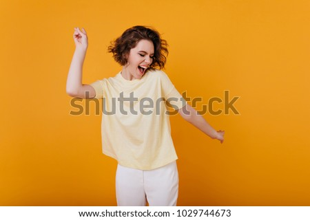 Pale brown-haired girl in yellow t-shirt dancing with inspired face expression. Active young woman in casual summer outfit having fun indoor.