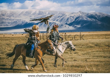 SAGSAY, MONGOLIA - SEPTEMBER 28, 2017: young woman berkutchi eagle hunter and her father. #1029850297