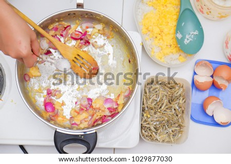 Young asian boy stirring ingredients for cooking homemade spicy fried rice #1029877030