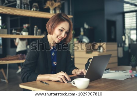 Asian business woman working in in coffee shop cafe with laptop paper work  (Business woman concept.) #1029907810