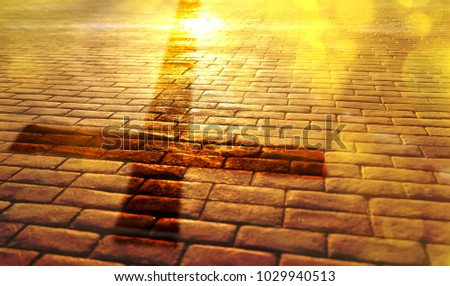 Representation of the way of salvation in the Christian religion with shadow of the cross on stone slabs and golden reflection of the sun